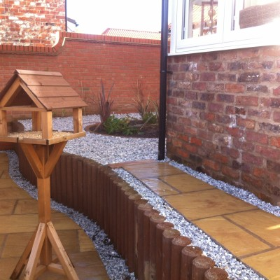 Raised patio using wooden poles, gravel and planting area